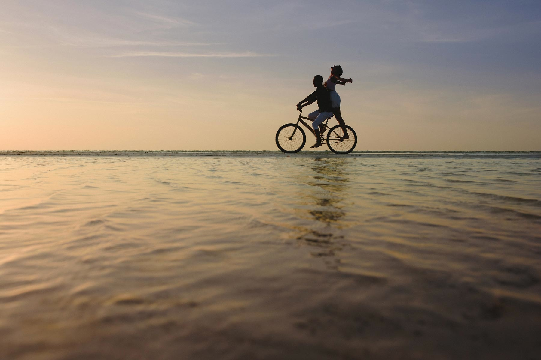 couple riding bike in holbox